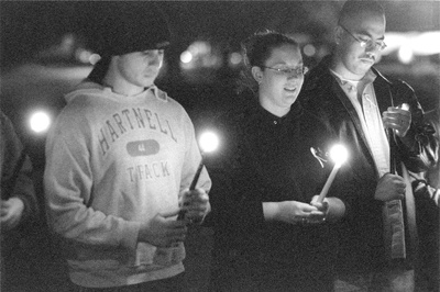 ULV students Bernard Corpuz, Renee Moore and Gabriel Dorantes formed a circle along with other students around the Rock Tuesday for an informal candlelight vigil. Moore, an R.A. at Stu-Han, organized La Verne's part in this nationwide event in recognition of support for the U.S. troops in Iraq. The candlelight vigil was not meant as an attempt to take sides for or against war with Iraq, but rather to give support to the troops through prayer and recognition and to bring a sense of comfort to family and friends with loved ones serving overseas in the military. / photo by Bailey Porter