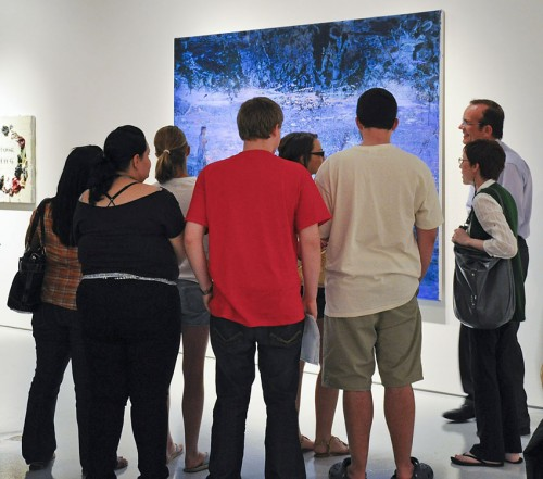 """Al Clark, associate vice president for academic affairs, leads a discussion with his Honors Colloquium class while viewing """"Runaways (From the River),"""" painted in 2008 by Angela Dufresne. The first Harris Gallery opening for the year, which began on Tuesday, brought together four artists in the exhibition """"Psychic Hearts,"""" curated by Director of Galleries Dion Johnson. The exhibit runs through Oct. 8. The gallery hours are Monday through Thursday from 11 a.m. to 4 p.m. and by appointment. / photo by Erin Maxwell"""