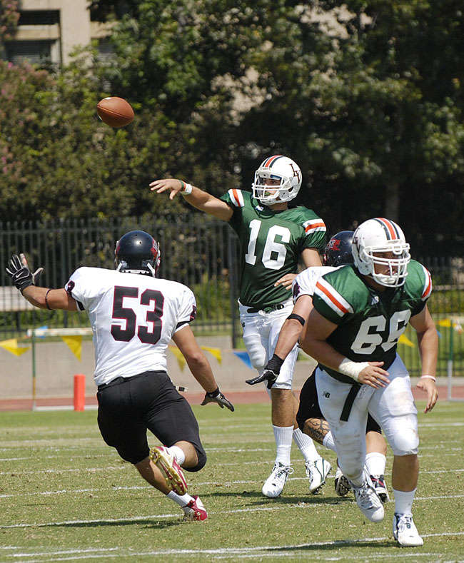 La Verne quarterback Christian Winnewisser completes a pass over Whitworth defenders Jeff Erlenmeyer and Travis Niles for a short gain in the third quarter. Whitworth toppled the Leopards, 21-9, with the help of two fourth quarter touchdowns. / photo by Christopher Guzman