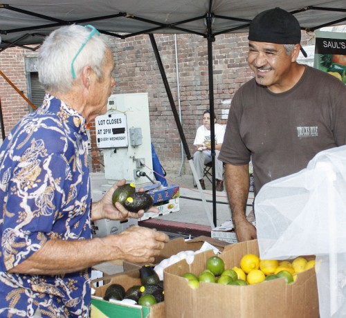 Michael Fleming of Pomona and Saul Jimenez of Saul's Family Produce in Claremont met at the Pomona Farmers Market on Sept. 16. The Farmers Market features popcorn and smoothie stands, as well as a live band playing Latin dance music. The market runs from 4 p.m. to 8 p.m. every Wednesday at Garey Avenue and Second Street in Pomona. / photo by Stephanie Arellanes