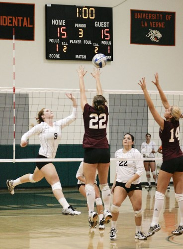 La Verne setter Anna Calmer spikes a point against Redlands outside hitter Jackie Hamilton (No. 22) and middle back Emily Capozzoli (No. 14) with help from setter Yesenia Lopez. The Leopards chained up the Bulldogs, 3-1, Tuesday on the Frantz Athletic Court. The team opens the SCIAC tournament at 5 p.m. Friday against Cal Lutheran at Currier Gymnasium in Redlands. / photo by Cindy Harder