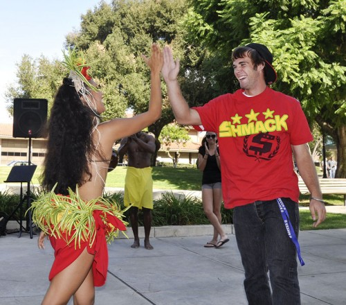 """Freshman Anthony Bennett is congratulated by an Isle Entertainment dancer after being called up from the audience to join in a tradition at The """"Gilligan's Island"""" Hawaiian Lunch on Wednesday. The lunch in Sneaky Park was part of the TV Land Homecoming theme. / photo by Erin Maxwell"""