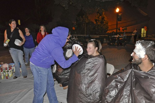 Everyone who attended the pep rally Friday evening was given the opportunity to throw a whipped cream pie at members of the Homecoming Court. Senior Nataly Escobar gave senior Samantha Cacchione, who was eventually elected Homecoming queen, her first cream pie of the night. / photo by Erin Maxwell