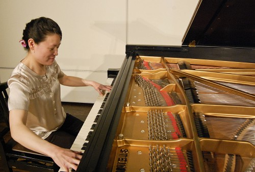 """Yih-Mei Hu, a visiting professor at Scripps College, performed music of Claude Debussy, George Crumb and Franz Liszt as a part of the Friday Noon Concert series in Balch Auditorium on Feb. 19. Each piece was unique, including Crumb's """"Five Pieces for Piano,"""" which required not only the playing of the keys but the plucking of the piano strings. / photo by Christopher Guzman"""