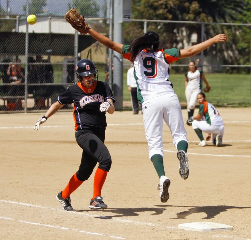 Reaching in vain, Amanda Hastings misses the errant throw as Nicole Hannasch runs to first base during the first inning of Saturday's game. The Leopards mortally wounded the Tigers with a 12-3 lead, triggering the mercy rule after five innings. / photo by Rafael Anguiano