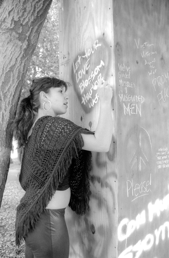 ULV alumna Carolina Quinteros uses the installation art piece at the Peace and Justice Festival, held in the Greek Amphitheater at Pomona College, to send her message. Spray paint and chalk were provided at the sight of the piece which is a wooden booth built by ULV senior Mabel Martinez. / photo by Jennifer Contreras