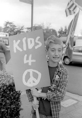 Eight year-old Kyle Bennett of La Verne thought it would be fun to make this sign. Bennett said he believes in peace and made the sign by himself. Bennett braved the four corners of the divided street rally in Claremont and said he was representating other children who share his beliefs. / photo by Jennifer Contreras