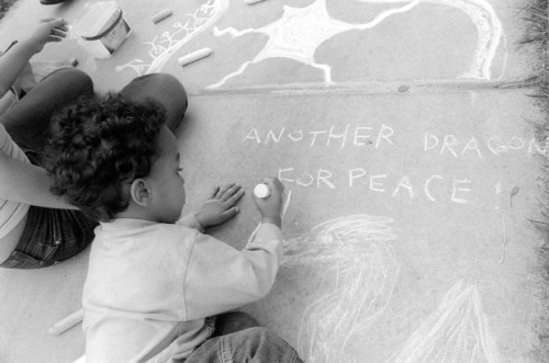 "Two-year old Levi Latty, who attended the Peace and Justice Festival in Claremont with his father Jahvi, joined other patrons in sidewalk art. Jahvi said that being an activist against the war, his presence was needed at the local event. ""It's a good place to network,"" he said. / photo by Jennifer Contreras"