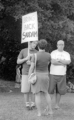 A center for controversy, a patron at the Peace and Justice Festival, who asked to remain anonymous, stood atop a small hill with his sign while various people confronted him about his intentions with the sign. / photo by Jennifer Contreras