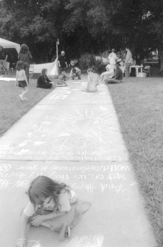 An entire walkway was decorated with colorful chalk at the Peace and Justice Festival. Gillian Tracy, 6, of Claremont sat in chalk to draw a rainbow on the floor. Also on the sidewalk were quotes, illustrations and peace signs. / photo by Jennifer Contreras