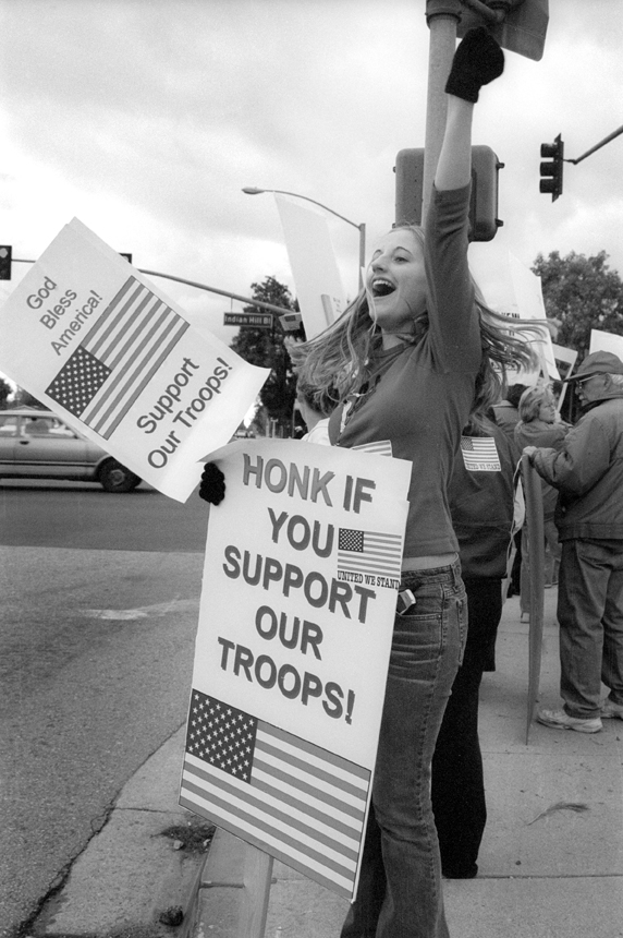 "Fifteen year-old Samantha Humphries of Claremont High School says, ""I feel that it is important to let the military know that we support them so they feel they have a reason to do this."" She and a group of friends were enthusiastic about their support for U.S. troops abroad and their rallying cheers solicited honks and shouts as they circled the intersection proudly. / photo by Jennifer Contreras"