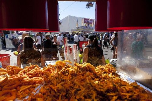 Piles of fried onion rings, French fries, zucchini and frog legs at Chicken Charlie's await orders from hungry fair goers. Chicken Charlie's is among the most popular fried food venders at the L.A. County Fair, offering everything from vegetables to fish and desserts, including Oreos and Klondike Bars. The business has two separate locations at the fair. / photo by Garrett Gutierrez