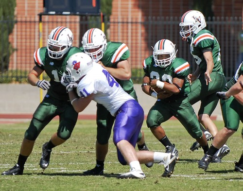 La Verne senior Devon Libran carries the ball up the middle for a short gain, Saturday in the Leopards' game against Linfield. The Wildcats controlled the pace of the game, totaling more than 400 yards on offense. The Leopards dropped the game, 30-3. / photo by Christopher Guzman