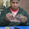 "Freshman business administration major Christopher Pulu volunteered to make bracelets on Monday for CAB's ""Bracelet Making for Children with Down Syndrome."" Each bracelet was made with letter beads, creating encouraging words, such as laugh, life and faith. CAB invited volunteers to the philanthropic event outside the Campus Center. Blue and yellow ribbon pins were handed out at the event to help raise awareness for the Down Syndrome organization. / Photo by Jakeh Landrum"