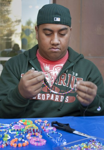 """Freshman business administration major Christopher Pulu volunteered to make bracelets on Monday for CAB's """"Bracelet Making for Children with Down Syndrome."""" Each bracelet was made with letter beads, creating encouraging words, such as laugh, life and faith. CAB invited volunteers to the philanthropic event outside the Campus Center. Blue and yellow ribbon pins were handed out at the event to help raise awareness for the Down Syndrome organization. / photo by Jakeh Landrum"""