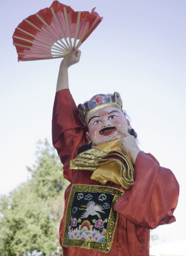 The god of fortune, as portrayed by Sydney Wang, proclaims the Year of the Rabbit at the Chinese New Year Celebration by handing out treasure-filled envelopes to many lucky onlookers, who gathered for the event, Feb. 3 in Sneaky Park. / photo by David Bess
