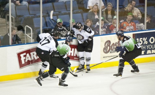 """The Ontario Reign's Jordan Morrison and alternate captain Luke Beaverson struggle to gain control of the puck along the boards as the Reign face down divisional rival the Las Vegas Wranglers on March 12 at Citizens Business Bank Arena for """"Go Green and Teacher Appreciation Jersey Night."""" The Reign beat the Wranglers, 3-1, following a 7-4 loss the night before. / photo by Warren Bessant"""
