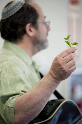 "Paul Buch, cantor of Temple Beth Israel of Pomona, describes the symbolism of the bitter herb at the Model Seder Tuesday, in the West Dining Room. Buch included an explanation of the Passover meal and sang traditional Jewish songs as well a few humorous non-traditional songs and a soulful rendition of ""Let My People Go."" / photo by David Bess"