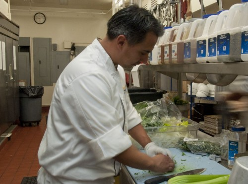 The University's new head chef Justin Alarcon prepares side dishes of vegetables for lunch in Davenport Dining Hall. Working for Bon Appetit, La Verne's new food service provider, Alarcon's responsibilities include training kitchen staff. He has been a chef for 10 years. / photo by Denisse Leung