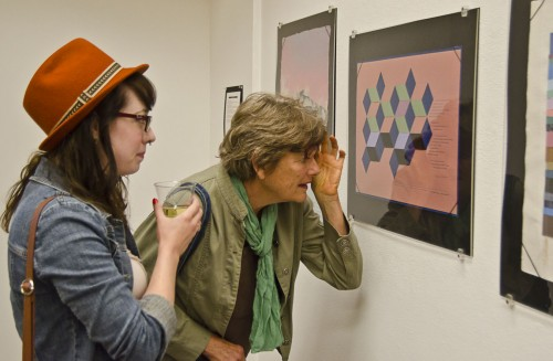"""Gallery visitors Linda Dare and Stephanie Froehner take a closer look at the letterpress works in the """"Women Over 25: Printing Letterpress for Over a Quarter of a Century,"""" exhibit in the Clark Humanities Museum in Claremont. The particular piece they are observing has paper cut-outs woven together and pressed flat. The Scripps College Press celebrated the 70th anniversary of its founding class with the exhibition. The exhibition features the work and dedication of women who have spent 25 years or more working with the craft of letterpress printing. The collection can also be found in Scripps College's Denison Library. / photo by Zachary Horton"""