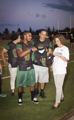 Linebacker Fillip Marcelin surprises University President Devorah Lieberman with a No. 18 Leopard football jersey while pumping up the full crowd at La Verne's first pep rally in more than twenty years. During her speech, the president praised the team's hard work and wished them luck on their next game. / photo by Mitchell Aleman