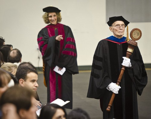 As Bob Neher, professor of biology and chair of the Natural Sciences Division leads the procession, he carries the new University mace. President Devorah Lieberman asks students and attendants to look his way. Neher wears white gloves to protect the mace from the touch of human hands. / photo by Zachary Horton