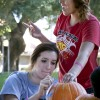 Juniors Michelle Web and Christine Kinney carve a jack-o'-lantern at Hagrid's Pumpkin Patch hosted by CAB in Sneaky Park Thursday. The tradition of carving pumpkins, which originated in Ireland, came from the folklore story of Stingy Jack and his deal with the devil to not claim his soul at death. / photo by Scott Mirimanian