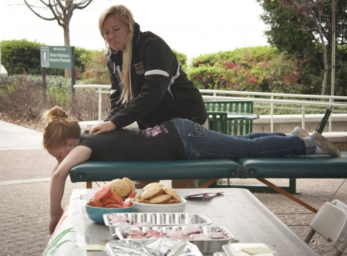 Junior Jessica Gerard stops by to get a massage from Ariel Guldstrand, a junior athletic training major, outside the Athletic Pavilion on Tuesday. The Athletic Training Student Club hosted a fundraiser in the Johnson Family Plaza for the Brain Injury Association of California to help raise awareness, educate about injuries and advocate for those affected by brain injuries. Massages were priced at a dollar a minute. Baked goods also were sold; they included muffin tops, brownies and cookies. / photo by Brittney Slater-Shew