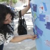 """Senior Angela Rios places a signed puzzle piece on one of the oak trees outside the Campus Center on Monday as part of the """"Light it Up Blue"""" event. The event was sponsored by the College Panhellenic Association to raise awareness about autism. / photo by Debra Escobar"""