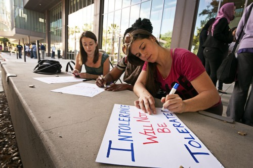 Rachael Sullivan, Sonja Assouline and Sarah Leclerc, first year clinical community psychology students, create signs to be placed in the Peace Pavilion in front of the Campus Center Wednesday March 4. Students marched from The Rock to the Campus Center after the Hoodies and Hijabs for hope and peace awareness gathering. / photo by Scott Mirimanian