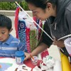 Five-year-old Steve Aguilar decorates a Koi shaped flag for his mother Norma Aguilar at the Japanese Culture Club's Children's Day celebration on May 3 in Sneaky Park. Children's Day became a national holiday in Japan in 1948 and is celebrated every year on May 5. Families fly Koinobori, or carp-shaped flags, and eat traditional rice dumplings and other treats to celebrate the occasion. /photo by Micah Scott Mirimanian