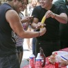 "To help spread awareness about the dangers of unprotected sex, Iota Delta hosted its second annual ""Latex or No Sex"" event outside the Campus Center. Sophomores Jose Ruelas and Irving Medrano practice by putting a condom on bananas handed out at the event. Soon after they enjoyed an ice cream sundae courtesy of the Iota Delta sorority. / photo by Mitchell Aleman"