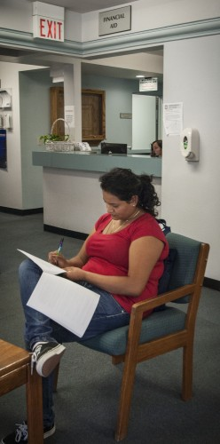 Rosalyn Reyes, a senior mathematics major, fills out financial aid paperwork in Woody Hall on Aug. 30. Statewide cuts have affected students receiving Cal Grants through their financial aid packages. Aid is determined heavily upon students' family income and financial need./ photo by Kelly Maggiulli