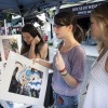 "On Thursday nights in Downtown La Verne, local venders come together and set up booths on ""D"" Street for a community farmers market. At this booth, sophomore communications major Jessica Rivera, sophomore criminology major Ashley Harris and sophomore broadcasting major Emily Morrow ask about the price on an Alice in Wonderland painting./photo by Ryan Gann"