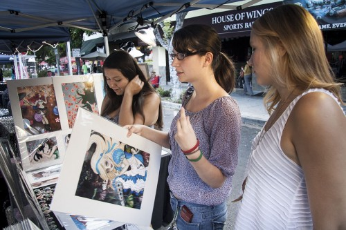 "On Thursday nights in Downtown La Verne, local venders come together and set up booths on ""D"" Street for a community farmers market. At this booth, sophomore communications major Jessica Rivera, sophomore criminology major Ashley Harris and sophomore broadcasting major Emily Morrow ask about the price on an Alice in Wonderland painting. / photo by Ryan Gann"