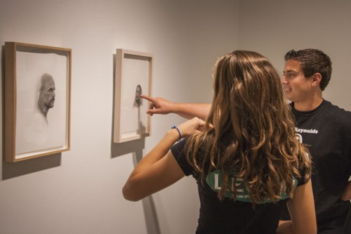 """Junior legal studies major Cameron St. George and senior child development major Andrea Arceo stop by the Harris Gallery between classes Tuesday, to view """"Visible,"""" the gallery's first exhibit of the year. Patrick Lee's graphite drawings """"Deadly Friends (Head #9)"""" and """"Deadly Friends (Head #2)"""" are among ten other pieces in the exhibit, which also features the work of Joe Biel, Mark Dean Veca and Eric Vahnker. The exhibit runs through Oct. 18. / photo by Ryan Gann"""