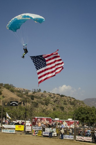 The San Dimas Sheriff's Skydiving Team drops from the skies to kick off the 2012 San Dimas Rodeo, bearing colored smoke and the American flag. The jump was followed by a rodeo competition, including bucking broncos, steer wrestling, and barrel racing. This is the rodeo's 18th year. / photo by Mitchell Aleman