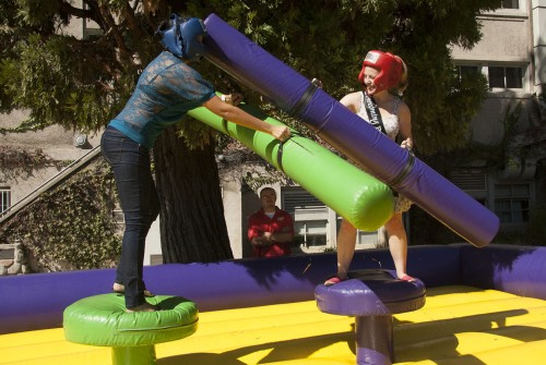 Senior math major Maggie Moreno loses a jousting match to senior social science major Jessica Gerard in the Quad on Tuesday. To kick off the voting for the Homecoming king and queen, the Campus Activity Board handed out Homecoming T-shirts to students who voted and offered activities including an inflatable rock climbing wall, decorating cardboard crowns and jousting. / photo by Ryan Gann
