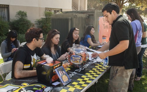 """To get students in the Halloween Spirit the Campus Activities Board hosted an event Tuesday at the Quad, where students can build their own haunted house out of graham crackers and frosting. Students also sent """"boo grams"""" to anyone living on campus. Pablo Garnica, junior psychology major sent a boo gram. Anthony Juarez, Caiti Helsper, Carina Gonzalez, and Cindy Vallejo are the cabbies that helped with the event. / photo by Kelley Maggiulli"""