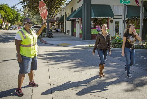 Tiffany Kinslow, who is also crossing guard for Roynon Elementary School, helps freshmen Ashley Valiente and Ashley Hernandez cross D Street on their way to class. After the city received complaints about pedestrians not paying attention, the La Verne Police Department hired crossing guards for two busy D Street intersections for the next three weeks. Their charge is to regulate car and foot traffic, which have been increasingly problematic thanks to record high enrollment at the University. / photo by Zachary Horton