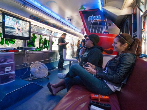 """Senior Victoria Moreno and Edgar Gomez, junior Spanish major, battle it out in """"Street Fighter"""" on Playstation 3 in the """"Thrills on Wheels"""" video game truck Feb. 13. Thrills on Wheels is a gamer's dream filled with arcade games and equipped with a couch, a Wii U, Playstation 3 and Xbox. The bus was parked at Sneaky Park and was open to any student who wanted to come in. /photo by Nicole Ambrose"""
