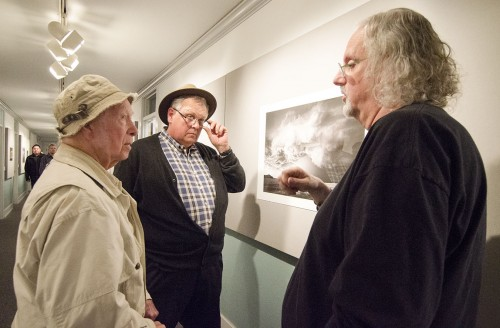 """University of La Verne alumnus Gerry Pence and his friend Doug Bro talk with photographer Mitch Dobrowner during the reception for Dobrowner's exhibition, """"Vital Firmament,"""" in the Carlson Gallery. Pence, who graduated from ULV in 1949, is an avid photographer. He discussed the use of both digital and film prints shown in the gallery. The exhibit runs through April 5. / photo by Mitchell Aleman"""