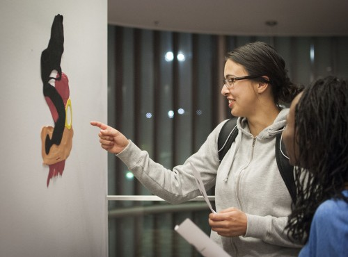 "Lindsey Foster, junior communications major, and Kyaundra Davis, sophomore movement and sport science major, admire the art piece titled ""Easy Rider."" The painting is part of ""Colorforms,"" a solo art exhibition of recent work by Los Angeles based artist, Megan Madzoeff. The exhibit will be displayed in the West Gallery, on the second floor of the Campus Center, though April 19. / photo by Kelley Maggiulli"