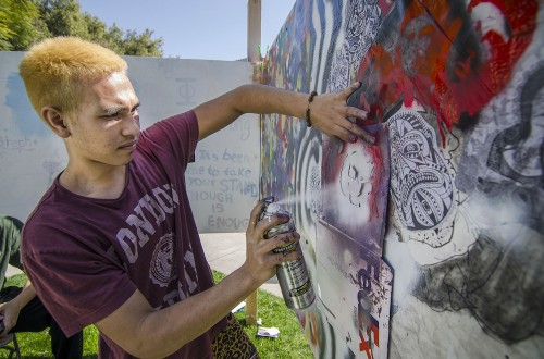 "On the cusp of spring break, sophomore art major Jourdan Simmonds, creates his anarchy themed graffiti piece for the event ""Empowerment through Art and Graffiti"" in Sneaky Park on March 15. Simmonds, from Ewa, Hawaii, is a member of the basketball team, playing point guard and shooting guard. The event was the second annual hosted by the anthropology department. / photo by Zachary Horton"