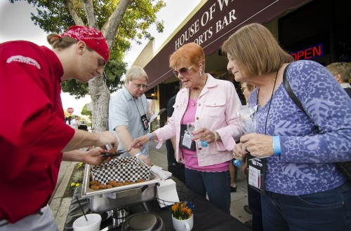 House of Wings sous-chef Justin Renauld offers Susanne St. Pierre and Toni Carone a selection of specialty wings to sample at the La Verne Wine Walk Saturday. The event brought in eight live bands to downtown La Verne, along with wine tasting, street artists and sample platters from local restaurants. The event sold out with more than 600 participants. / photo by Mitchell Aleman