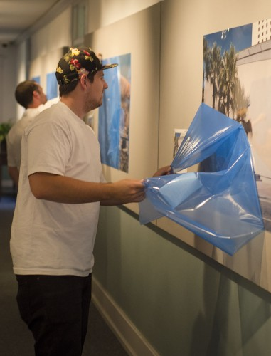 """Junior photography major Hunter Cole peels plastic off the latest installation in the Carlson Gallery, called """"Geolocation: Desertscapes,"""" by photographers Nate Larson and Marni Shindelman. The gallery will hold a reception at 6 p.m. Thursday at which photographers will be available to talk via video chat. / photo by Mitchell Aleman"""