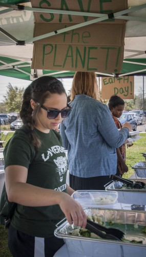 Junior athletic training major Lauren Martino attends the 50 Shades of Green Earth Day event hosted by CAB Monday in the South Quad. To promote sustainability CAB handed out reusable containers to everyone who attended. / photo by Kelley Maggiulli