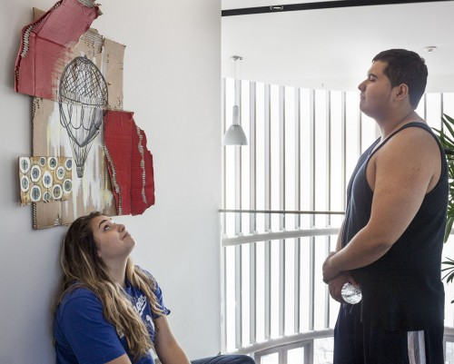 Junior art minor Nikki Godinez tells graduate student Mauricio Medrano the story behind her art installation. The piece represents what Godinez perceives to be her parents' disapproval of her art – and society's eyes always on her, Godinez said. The art department displayed students' art at the West Gallery in the Campus Center, for one day, April 30. / photo by Stephanie Ball