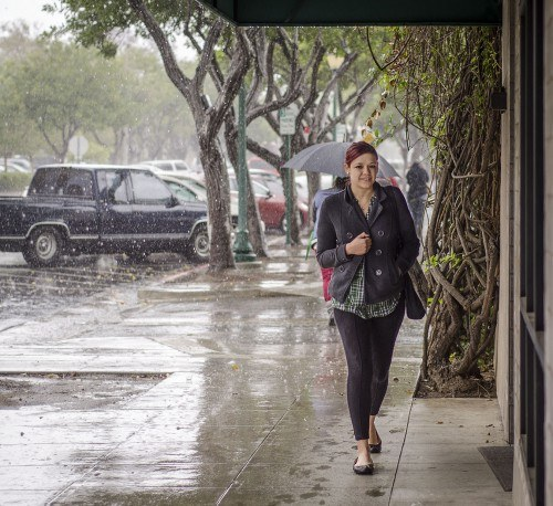 Senior criminology major Claudia Gonzalez steps under a canopy in front of the Barkley Building on D Street on her way to class Monday morning. The surprise rain showers continued all day Monday and into Tuesday morning. / photo by Zachary Horton