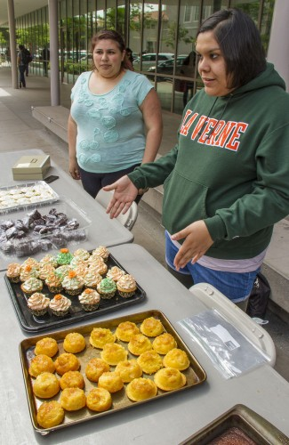 Sophomore journalism major Ingrid Rodriguez and sophomore music major Vicky Campos take the first shift selling homemade baked goods at the La Verne Choral Organization bake sale in front of the Campus Center Wednesday. The event was a fundraiser for the choir to perform at the Walt Disney Concert Hall this summer. Pineapple muffin turnovers, peanut butter cupcakes filled with jelly and chocolate brownies were among the items for sale. / photo by Ryan Gann